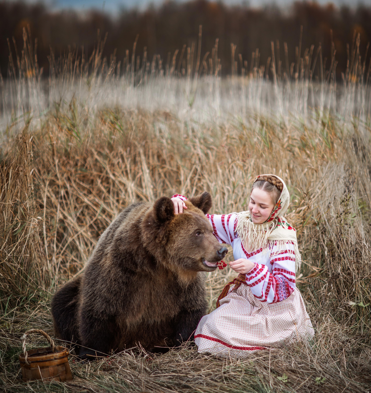 Девочка в национальном русском платье в поле кормит медведя