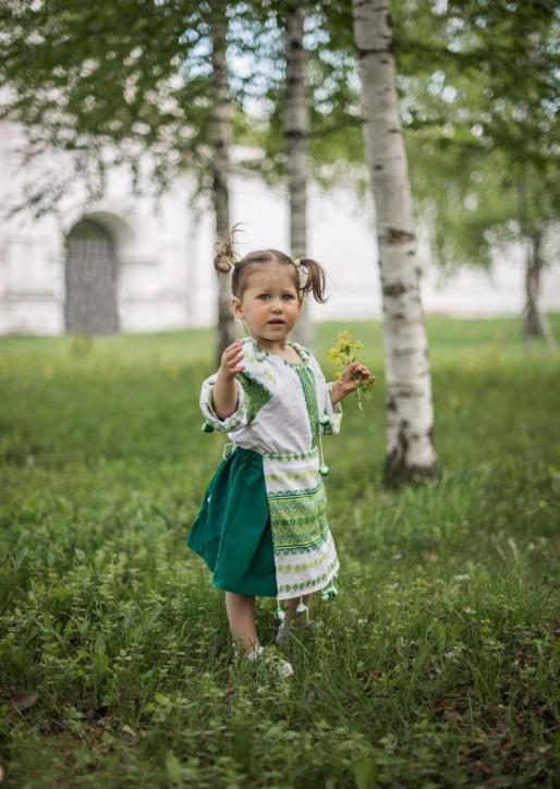 Девочка в березках в русском народном костюме на фоне измайловской усадьбы