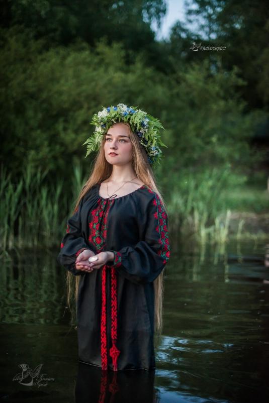 Девушка в славянском черном платье в воде со свечкой Купало