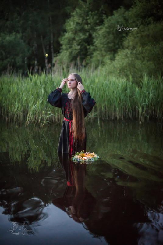 Девушка в славянском черном платье в воде пускает венок Купало