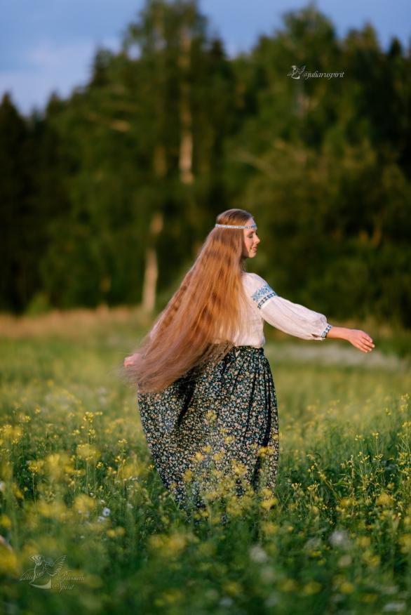Девушка в русском народном костюме на лугу в цветах