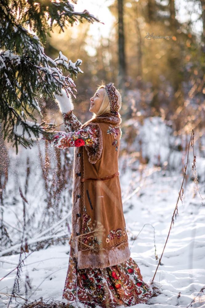 Девушка в жилете в русском стиле в лесу зимой