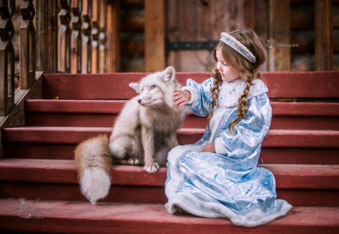 Девочка гладин лису на крылечке