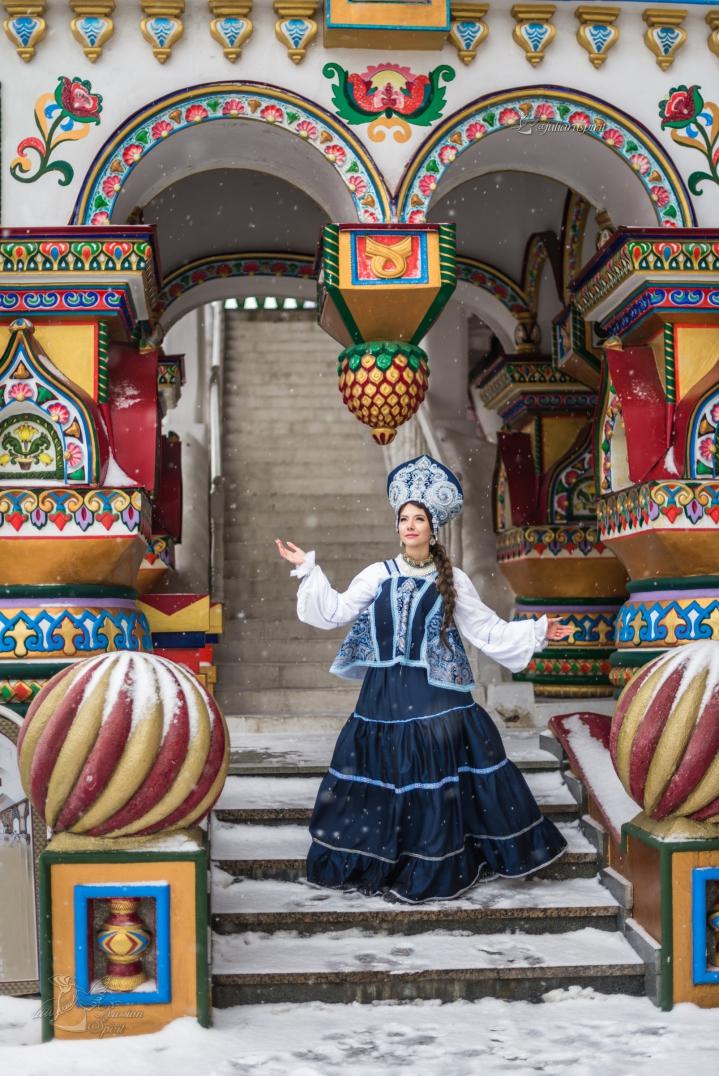 Фотосессия девушки на фоне деревянного кремля в русском стиле зимой