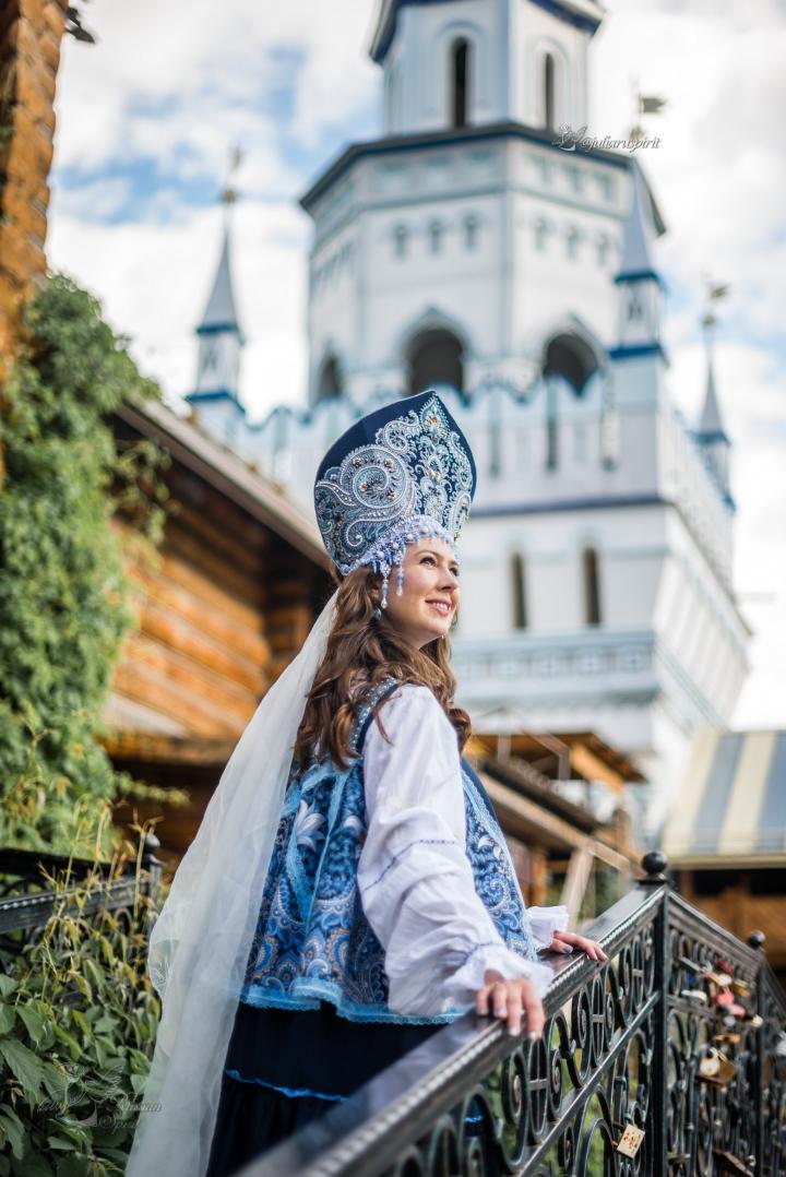 девушка на лестнице на фоне белокаменного кремля в русском стиле