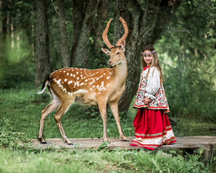 девочка в русском народном платье в лесу с оленем