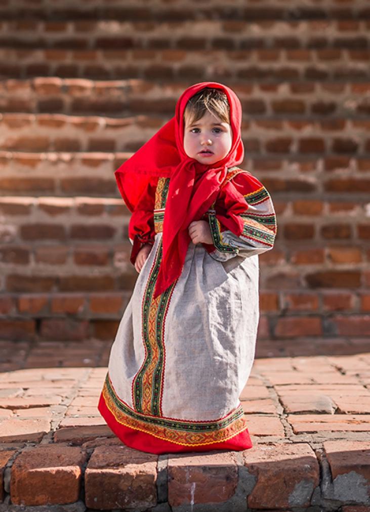 девочка в русском народном платье на фоне кирпичной стены