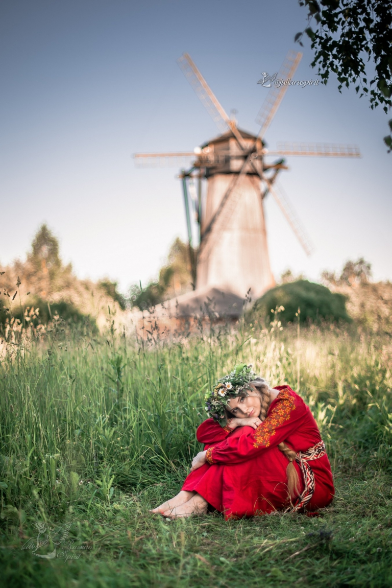 Девушка в красном славянском платье на фоне мельницы