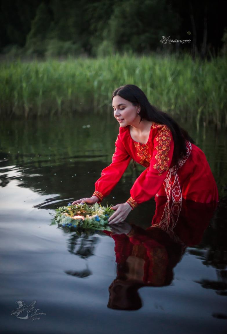 Девушка в красном славянском платье в воде с венком Купало
