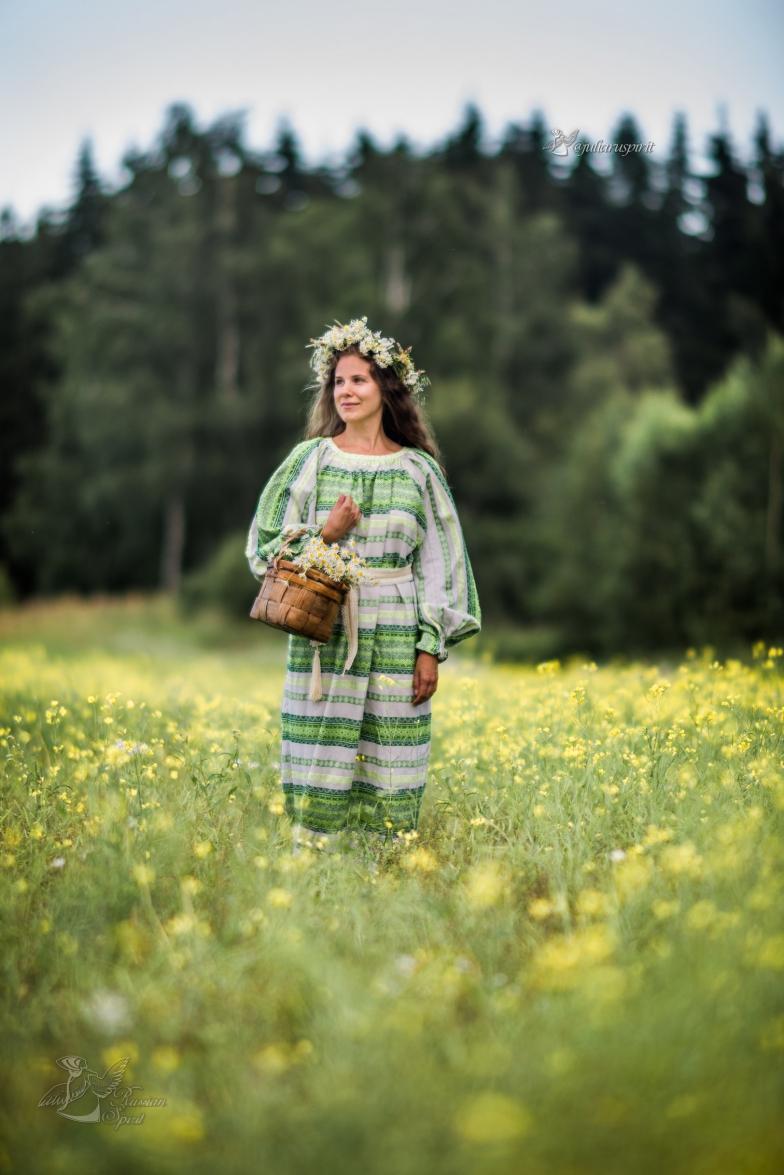 Девочка в национальном русском платье и венке в поле с корзиной ромашек