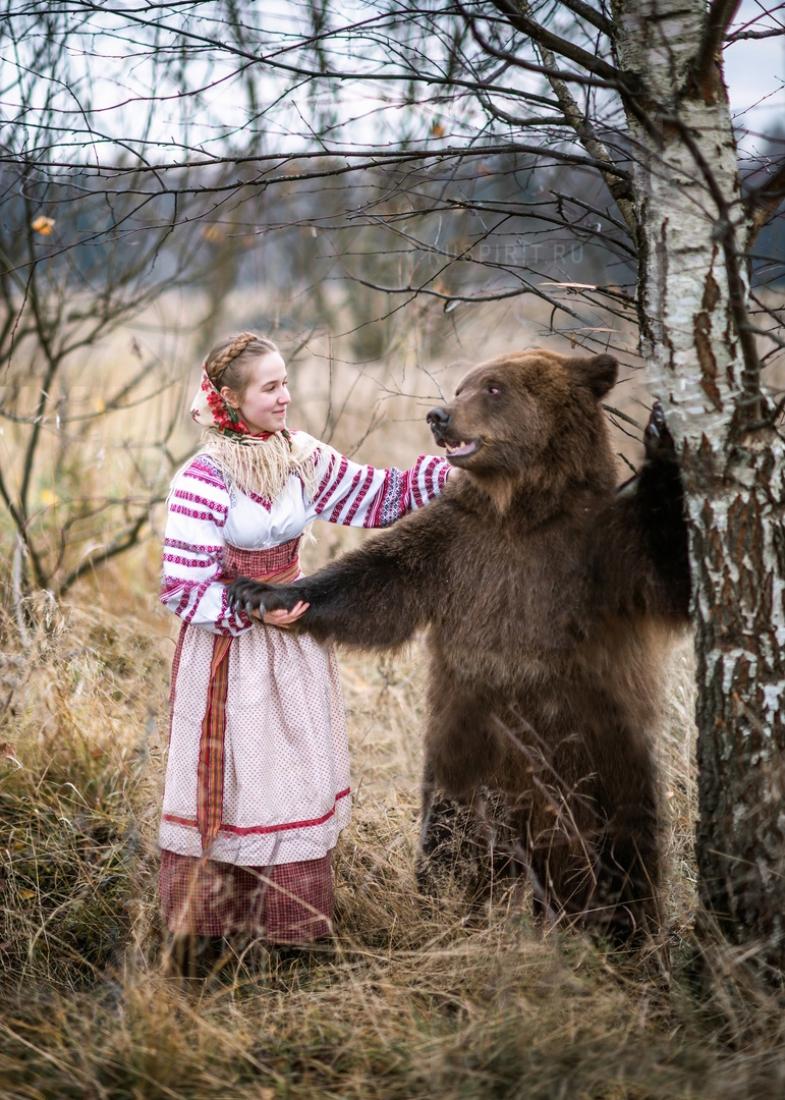 Девушка в русском народном костюме с медведем у берёзы