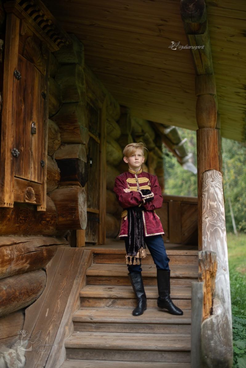 Мальчик в костюме в русском стиле на лестнице деревянного дома