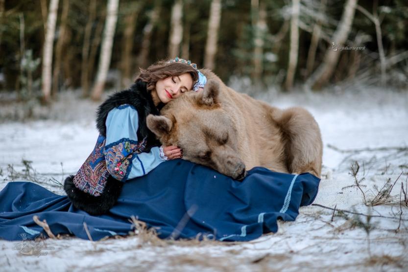 Девушка в костюме в русском стиле обнимашки с медведем
