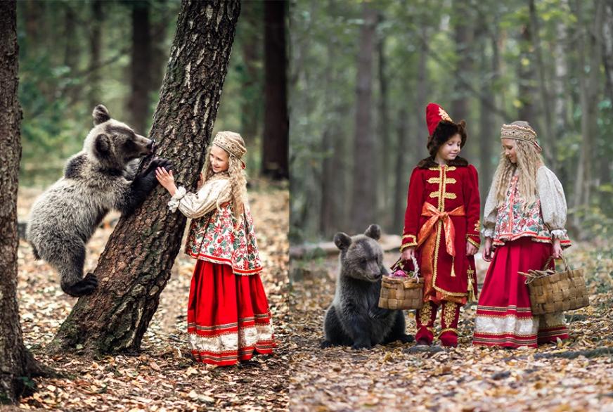 Девочка и мальчик в костюмах в русском стиле с медвежонком в лесу