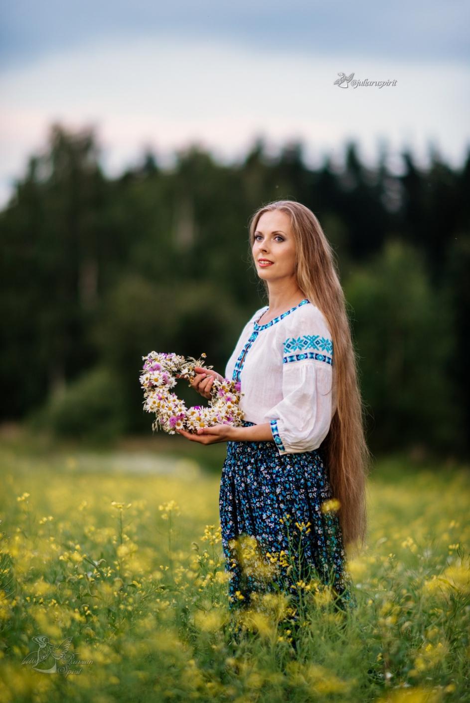Девушка в русском народном костюме на лугу с венком
