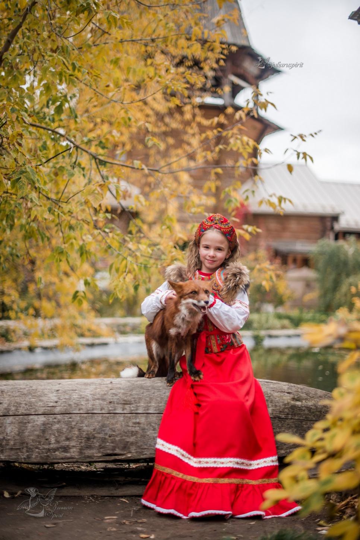 Девочка в платье в русском стиле с лисичкой у пруда