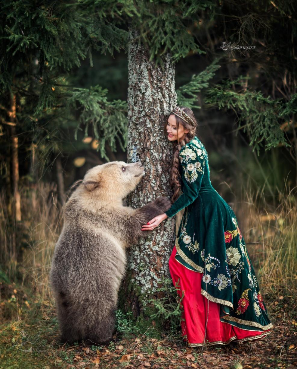 Девушка в вышитом узорами платье в кокошнике у березы гладит медвежонка